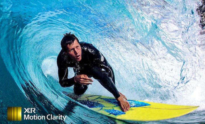 Imagen de un surfero en la ola mostrado en detalle y sin borrosidad